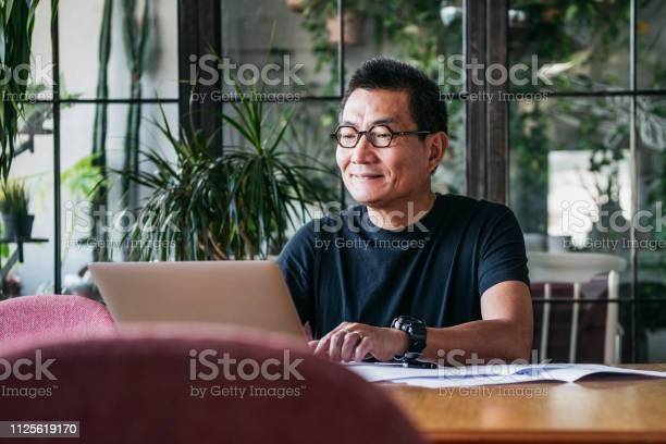 Photo libre de droit de Homme Chinois Souriant Travaillant Sur Ordinateur Portable À La Maison banque d'images et plus d'images libres de droit de 55-59 ans