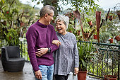 Front view of senior Chinese couple wearing casual clothing and laughing as they walk arm in arm outdoors.