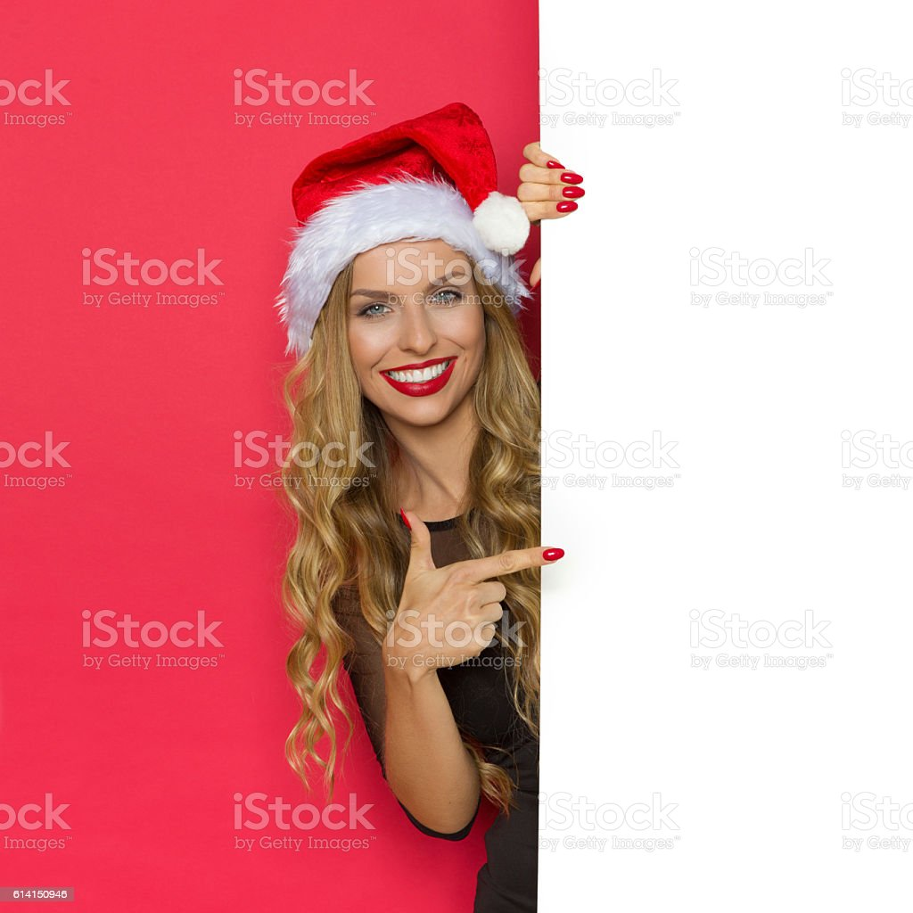 Smiling Christmas Woman Pointing At Placard stock photo