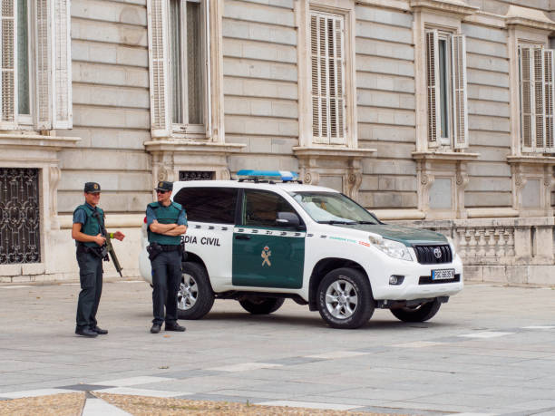 Smiling civil guardsmen on duty at Royal Palace of Madrid, Spain. stock photo