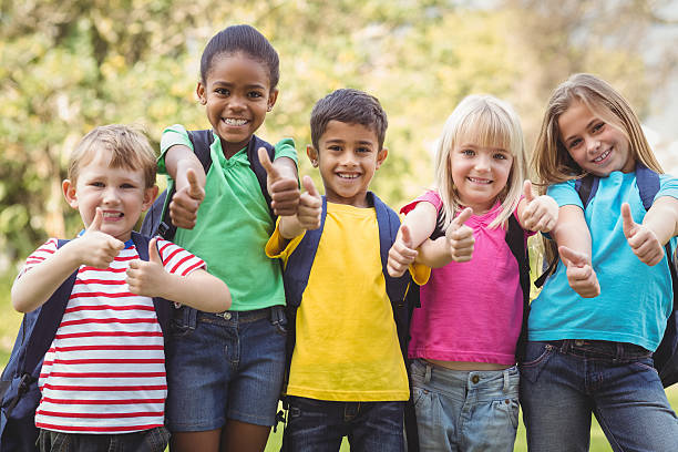 smiling classmates doing thumbs up to camera - back to school stock pictures, royalty-free photos & images