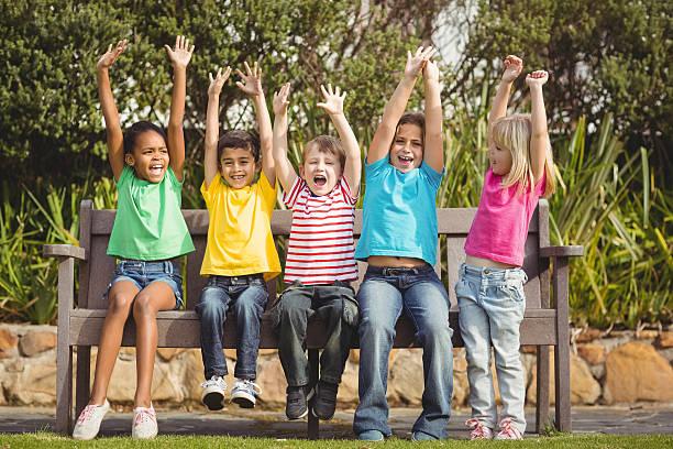 Souriant camarades de classe assis sur un banc et applaudissent - Photo