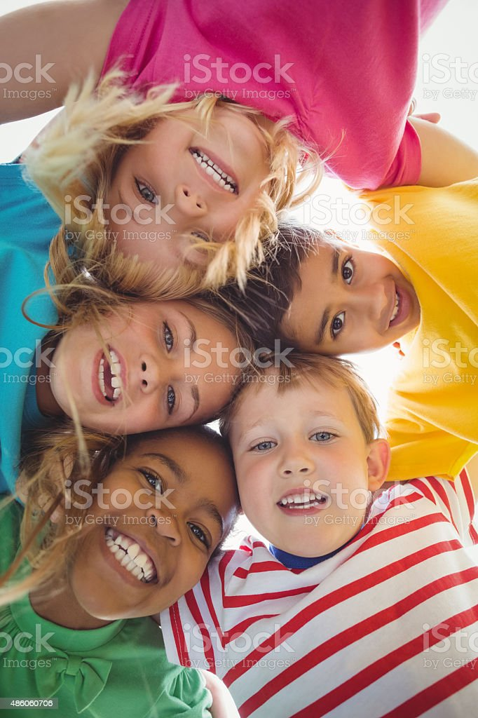 Smiling classmates with arms around looking down to camera stock photo