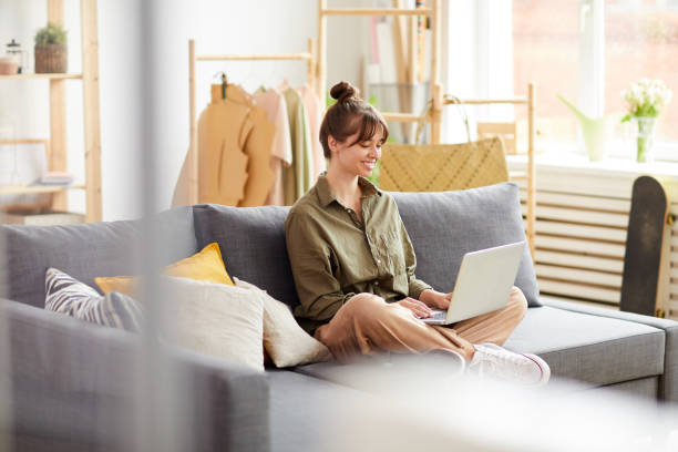 Smiling clothing designer with hair bun sitting on comfortable sofa and selling garments online stock photo
