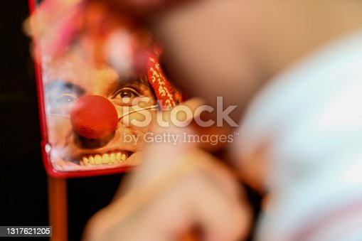istock A smiling clown looks at himself in a small mirror, he wears an Andean hat and a Peruvian sports shirt, on a black background. 1317621205