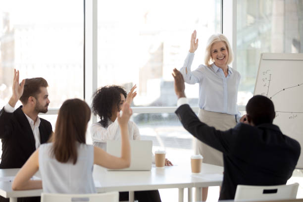 smiling coach raising hand with diverse team engaging in voting - employee engagement stock photos and pictures