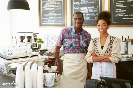 istock Smiling coffee shop owner with employee 466221345