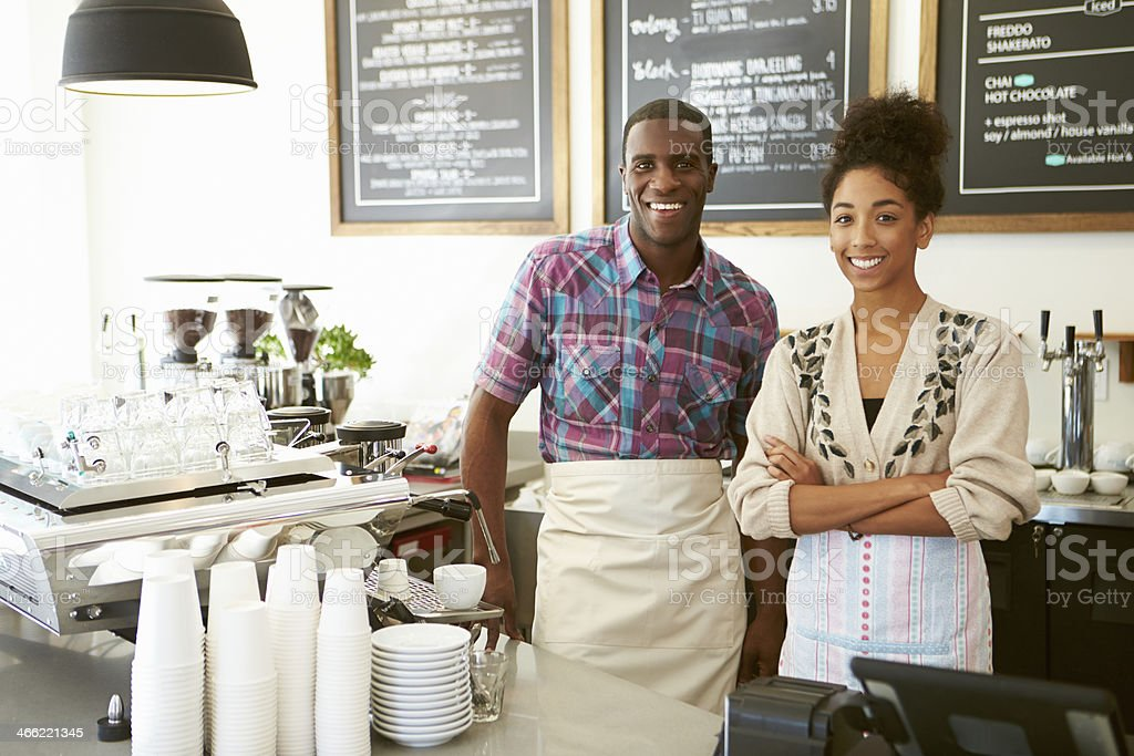 Smiling coffee shop owner with employee stock photo