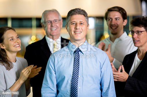 istock Smiling Colleagues Applauding to Proud Manager 648927660