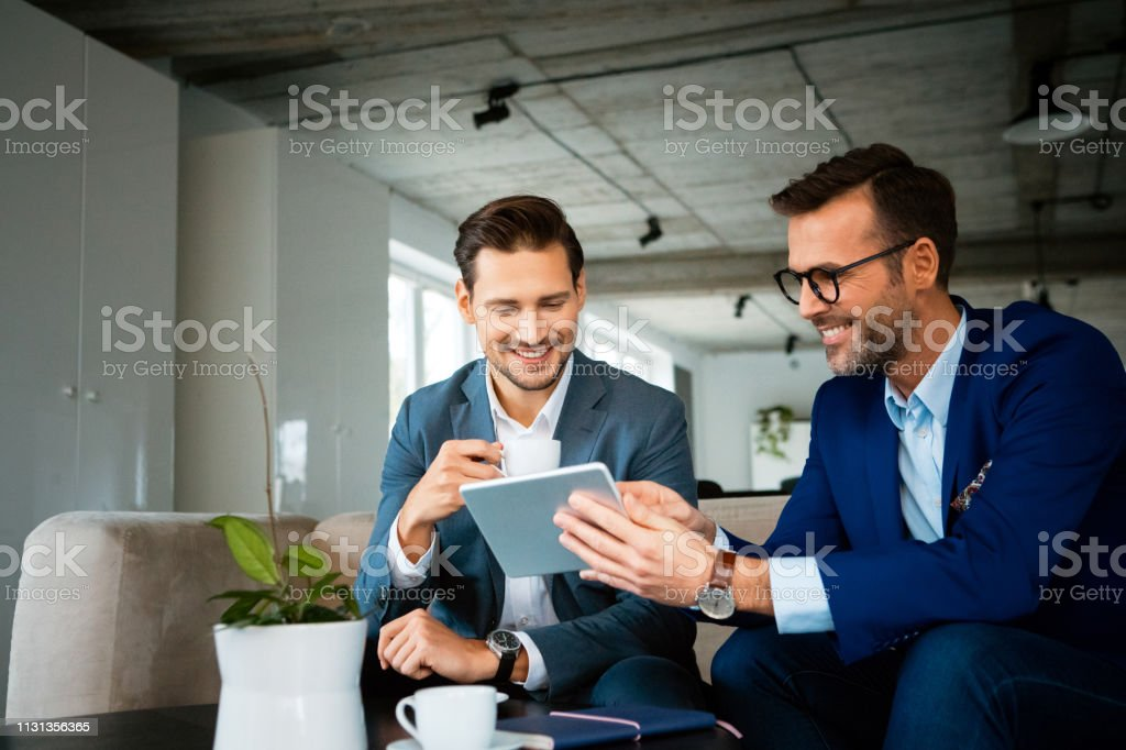 Smiling colleagues discussing over digital tablet Smiling male professionals discussing over digital tablet. Confident colleagues are planning strategy during meeting. They are working at creative office. 30-39 Years Stock Photo