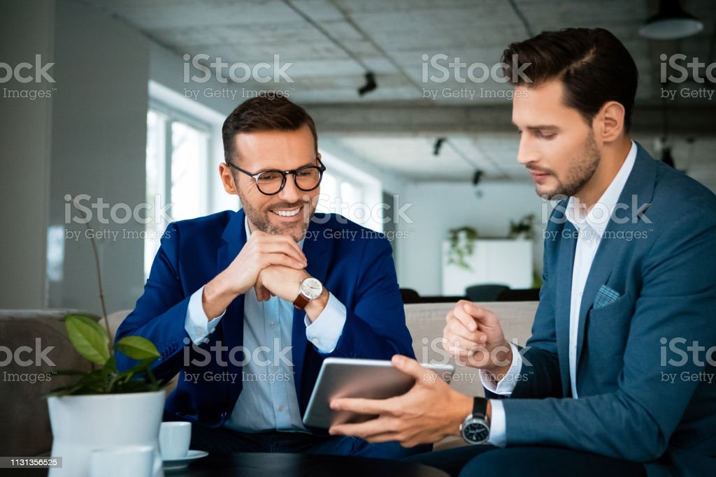 Smiling colleagues discussing over digital tablet Smiling colleagues planning strategy during meeting. Confident male professionals are discussing over digital tablet. They are working at creative office. 30-39 Years Stock Photo