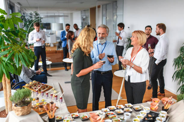 Smiling Colleagues Enjoying Food and Conversation at Party Elevated viewpoint of relaxed corporate colleagues enjoying savory dishes from buffet table at party to celebrate launch of new business. publicity event stock pictures, royalty-free photos & images