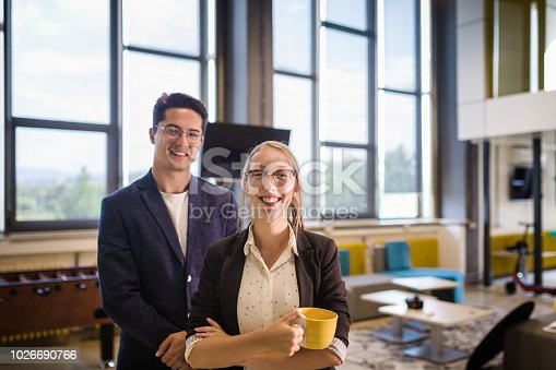 624700110istockphoto Smiling colleagues standing in their office 1026690766