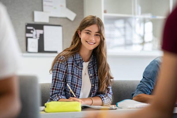 lächelnde college-mädchen im klassenzimmer studieren - jugendalter stock-fotos und bilder
