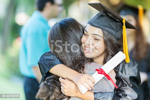 istock Smiling college grad embraces friend 614225316