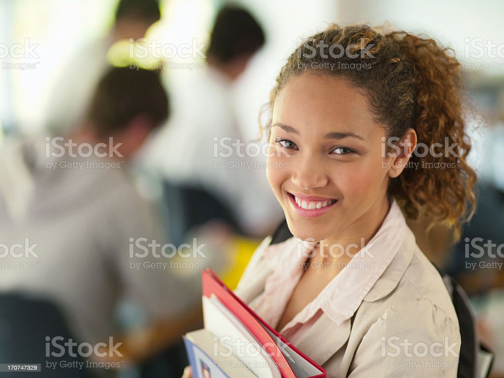 Smiling college student holding books stock photo