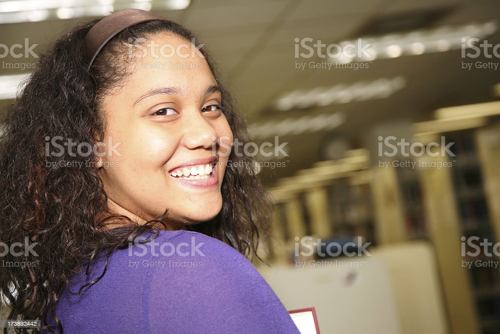 Smiling College Student Turning Back in the Library royalty-free stock photo