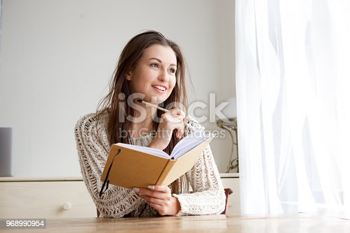 istock smiling college student with book and pencil 968990954