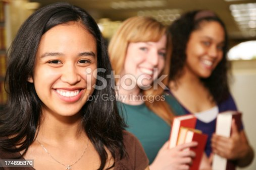 488149772istockphoto Smiling College Students in the Library 174695370