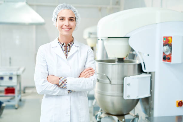Smiling confectioner standing at factory Beautiful confectionery factory worker standing in white coat with arms crossed smiling and looking at camera. hair net stock pictures, royalty-free photos & images