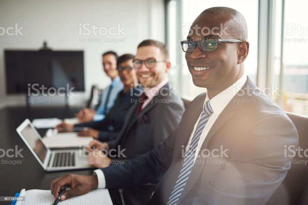 Smiling confident African businessman in a meeting Smiling confident African businessman in a meeting with a group of multiracial co-workers seated at a conference table in the office Adult Stock Photo