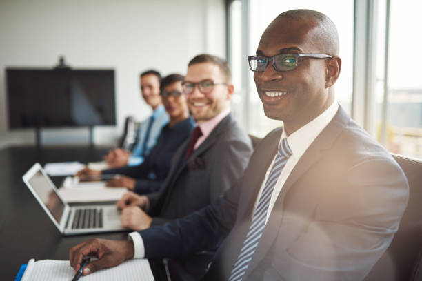 Smiling confident African businessman in a meeting Smiling confident African businessman in a meeting with a group of multiracial co-workers seated at a conference table in the office governing board stock pictures, royalty-free photos & images