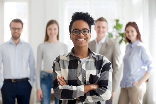 Smiling confident black company employee standing with colleagues at background Smiling confident black company employee standing with diverse colleagues at background, happy african female manager intern worker looking at camera, business leader coach in office portrait young girls on webcam stock pictures, royalty-free photos & images