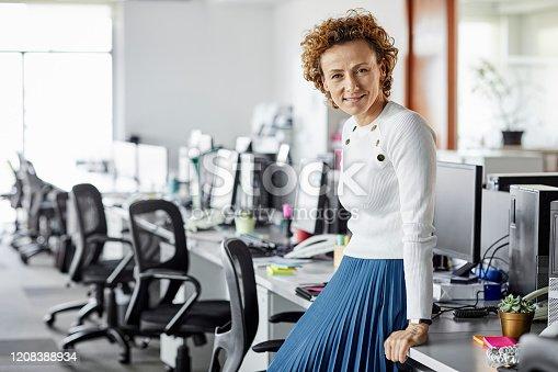 1150572074istockphoto Smiling confident businesswoman leaning on desk 1208388934