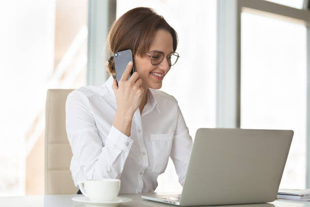 Smiling confident businesswoman making phone call using laptop in office Smiling confident businesswoman making phone call using laptop in office, successful millennial female boss talking on mobile at work, friendly secretary contacting consulting client by cellphone bingo caller stock pictures, royalty-free photos & images