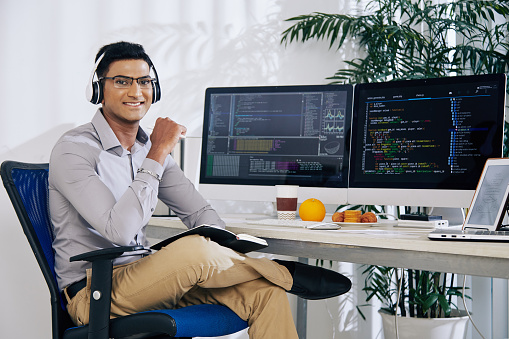 Portrait of smiling confident Indian coder sitting at his office desk with programming code on computer screens