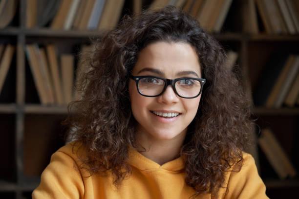 カメラを見て自信を持ってラテンティーン女子学校の生徒、大学生や大学の教師に微笑んでいます。幸せなヒスパニックの女性は、図書館の教室でポーズメガネを着用しています。ヘッドシ� - gen z ストックフォトと画像