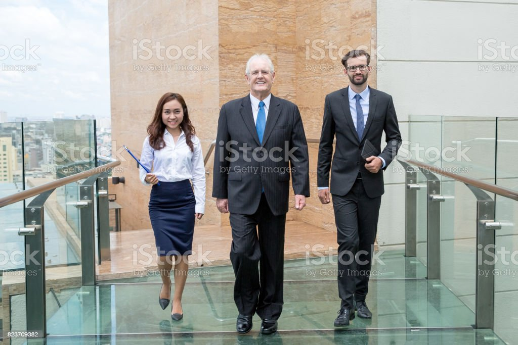 Smiling Confident Team Walking on Glass Bridge stock photo