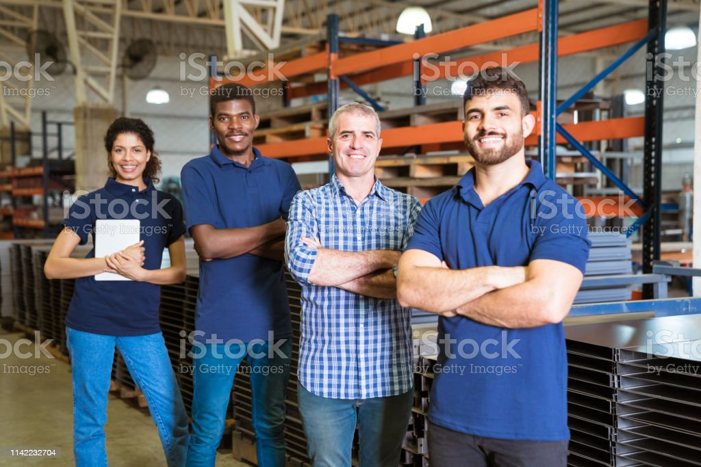 Smiling confident workers standing in industry Confident multi-ethnic workers in factory. Male engineer is standing with trainees. They are with arms crossed in factory. 20-24 Years Stock Photo