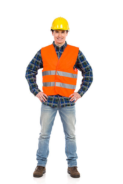 Smiling construction worker posing. Smiling construction worker in yellow helmet and orange waistcoat.  Full length studio shot isolated on white. reflective clothing stock pictures, royalty-free photos & images