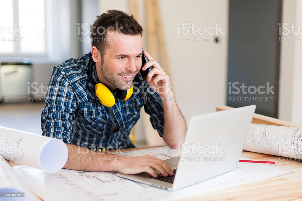 Smiling construction worker talking on mobile phone stock photo