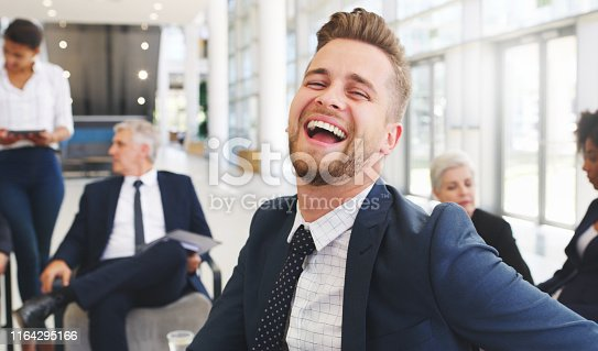 Cropped portrait of a handsome young businessman sitting and laughing while his colleagues work behind him in the office
