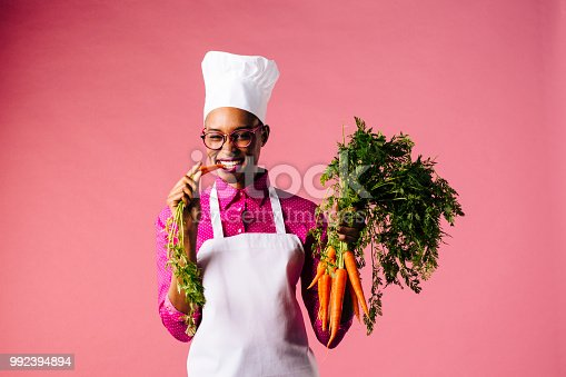 Smiling cook holding carrots, biting into one, isolated on pink