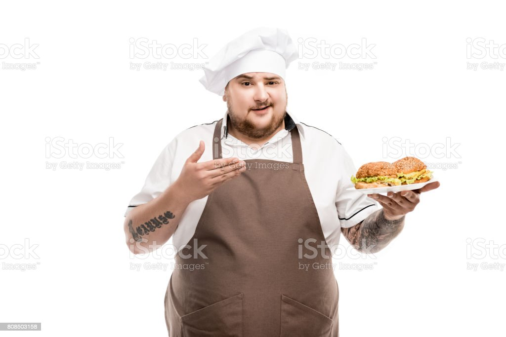 smiling cooker pointing at burgers on plate isolated on white stock photo