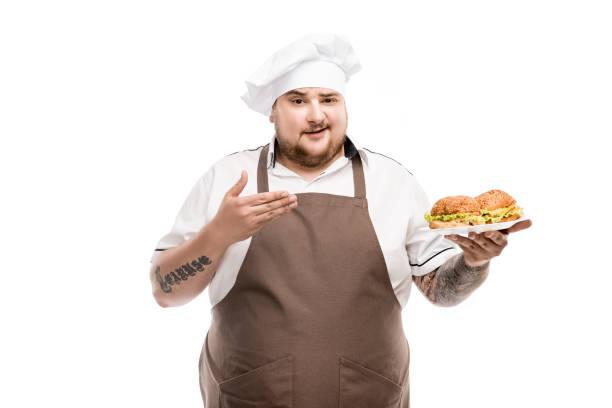 lächelnde herd zeigt auf burger auf platte isoliert auf weiss - grillschürze stock-fotos und bilder