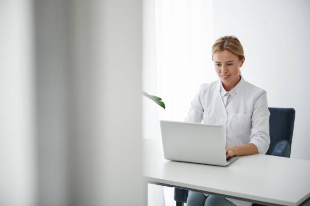 Smiling cosmetologist working on laptop while sitting at the table stock photo