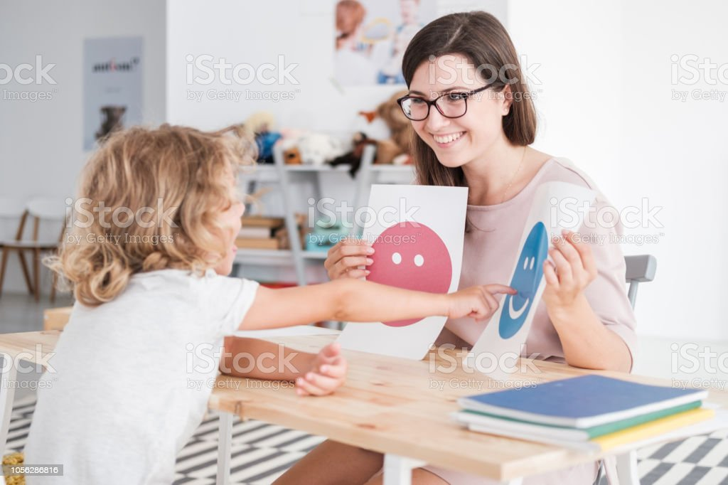Smiling counselor holding pictures during meeting with young patient with autism stock photo