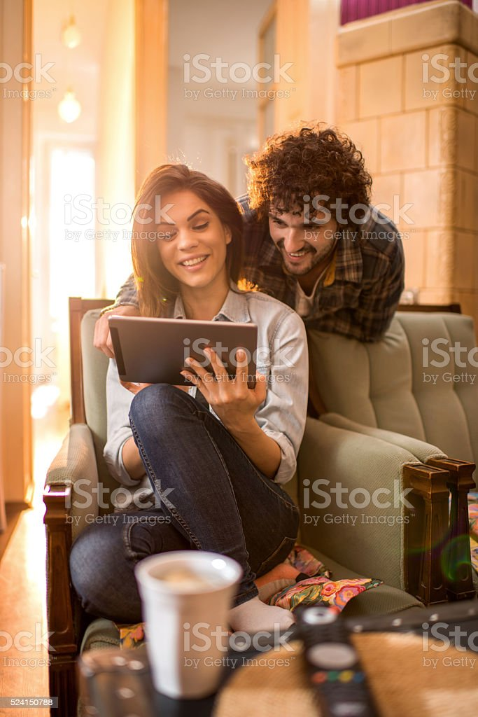 Smiling couple at home using touchpad. stock photo