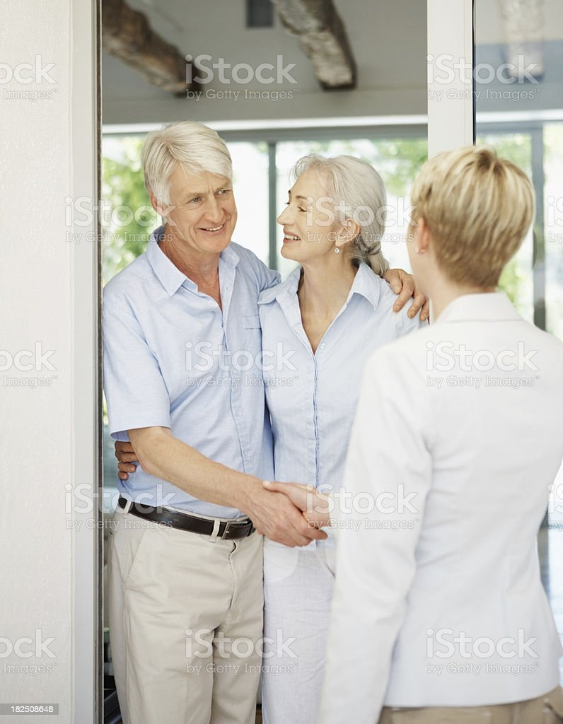 Smiling couple at the door welcoming a female royalty-free stock photo