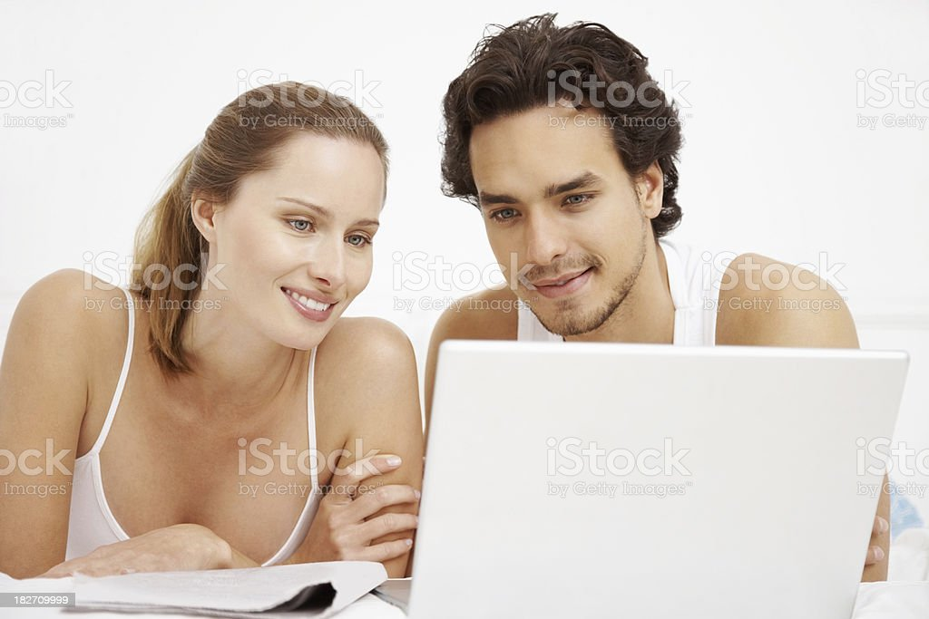 Smiling couple browsing the internet together on bed royalty-free stock photo