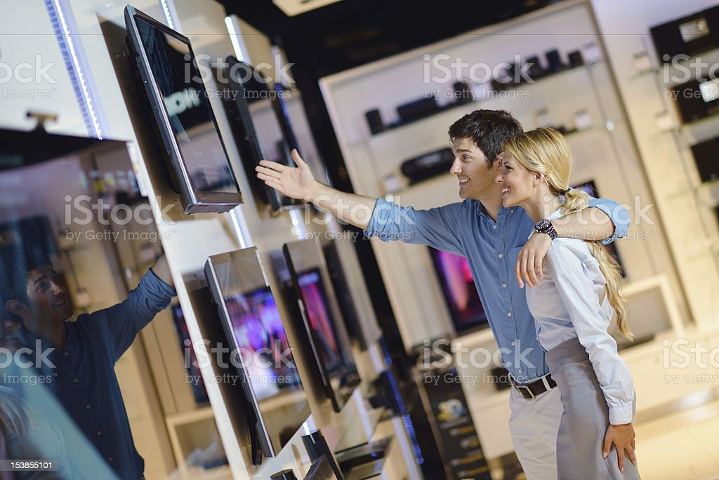 Smiling couple browsing TV choices in an electronics store stock photo