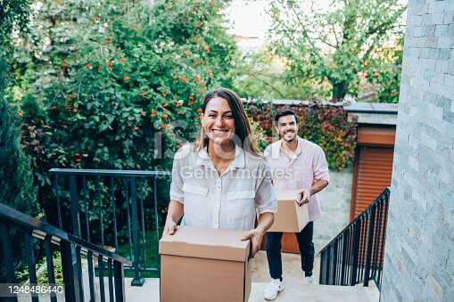 Portrait of happy young couple moving to new house with cardboard boxes. Couple move into their new home. Smiling couple carrying boxes into new home on moving day. Young family entering in their new house.