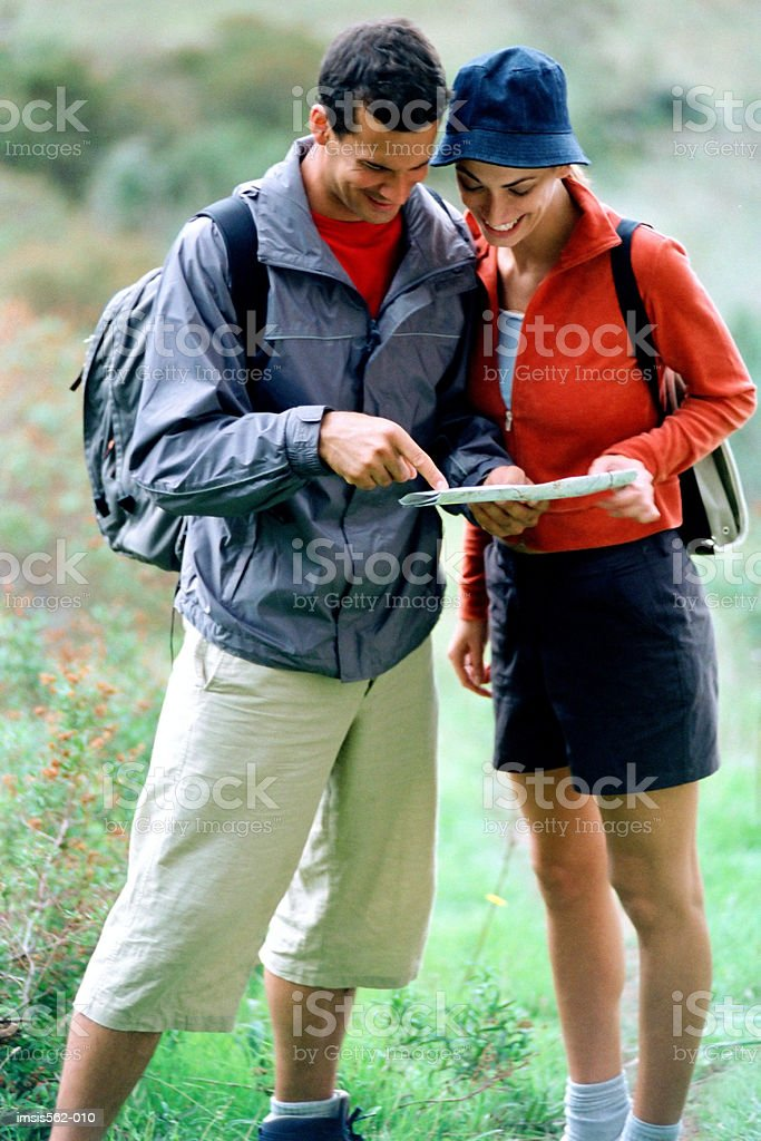 Smiling couple consulting map royalty free stockfoto