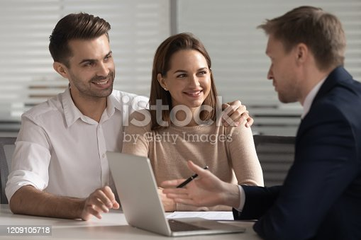 994164754 istock photo Smiling couple consulting with financial advisor or real estate agent. 1209105718