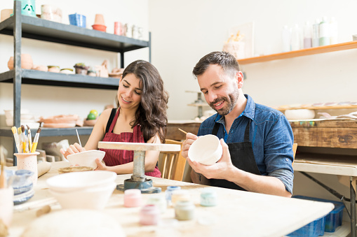 Smiling Couple Doing Creative Painting On Bowls In Pottery Workshop