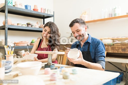 istock Smiling Couple Doing Creative Painting On Bowls In Pottery Workshop 1029864830